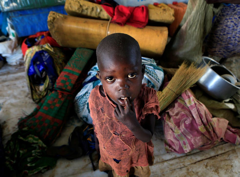 A displaced boy from South Sudan stands next to family belongings in Lamwo after fleeing fighting in Pajok town across the border in northern Uganda