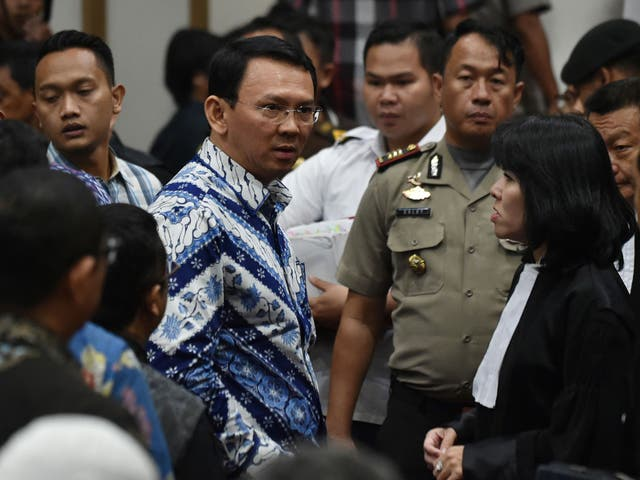 Jakarta's Christian governor Basuki Tjahaja Purnama (C), popularly known as Ahok, speaks to his lawyers after judges delivered their sentence during the verdict in his blasphemy trial
