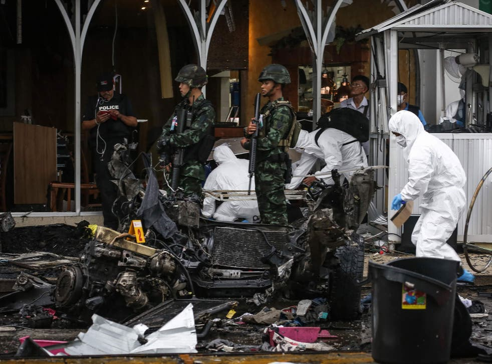 Thai soldiers stand guard as a forensics unit inspects the aftermath of a car bomb in front of Big C in the town centre of Pattani on 9 May