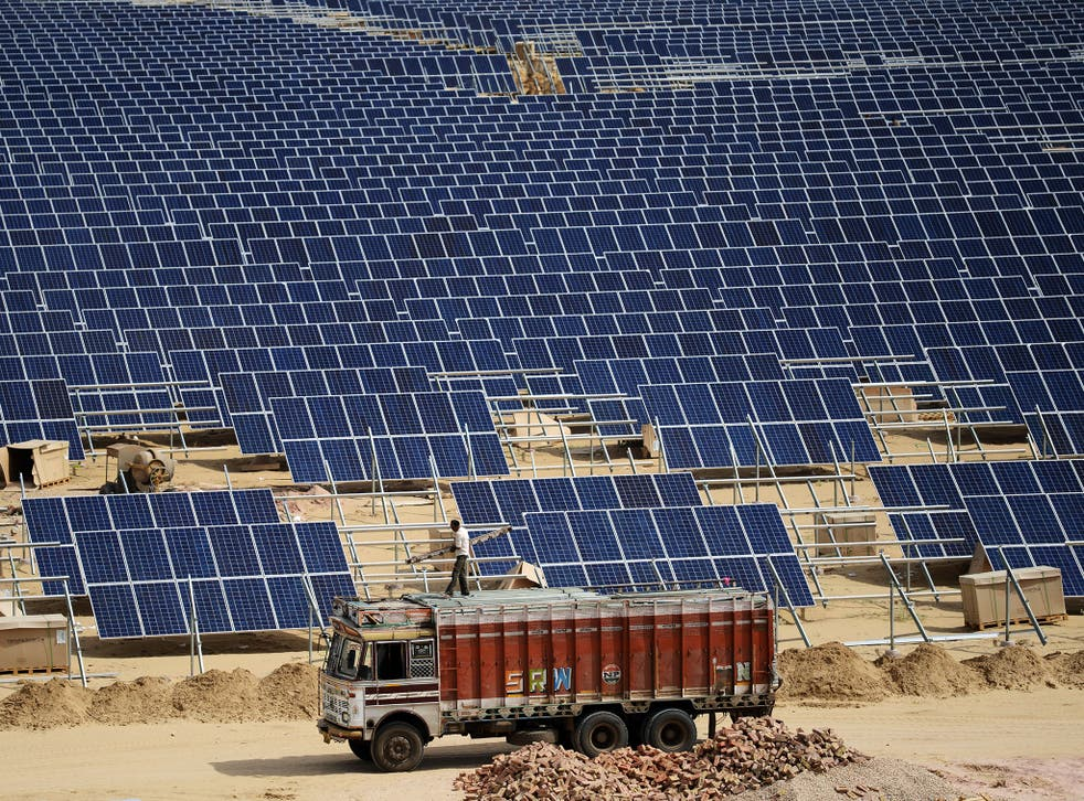 Indian engineer positions solar panels at the under construction Roha Dyechem solar plant at Bhadla in the western Indian state of Rajasthan