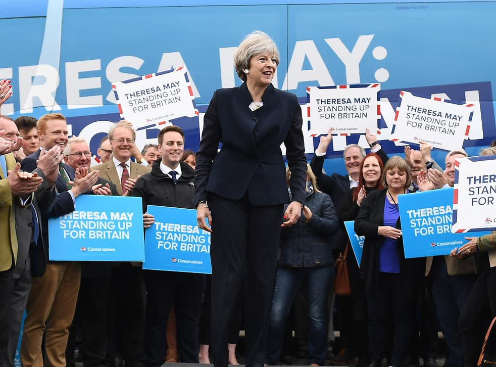 Theresa May speaks to party supporters in front of the Conservative Party's general election campaign battle bus