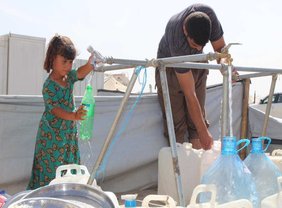 A little girl fills up a bottle with drinking water on 9 May 2017 in Hasensham IDP camp outside Mosul. Summer temperatures in Iraq hit a record 54 degrees Celsius last year