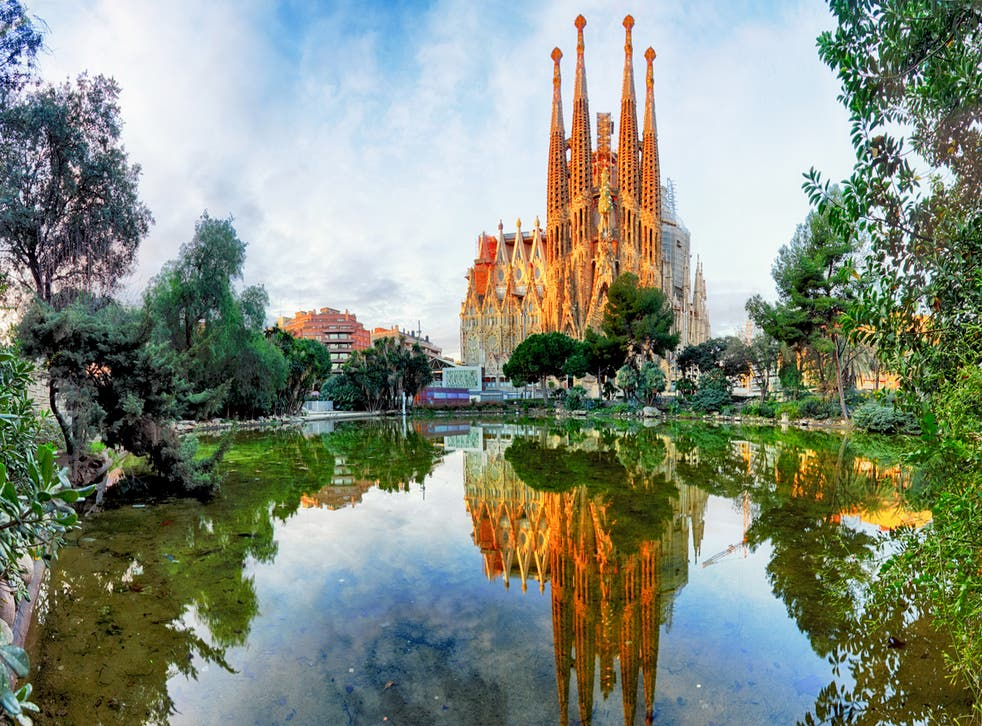 Barcelona's Sagrada Familia, looking across the lake in Placa de Gaudi gardens