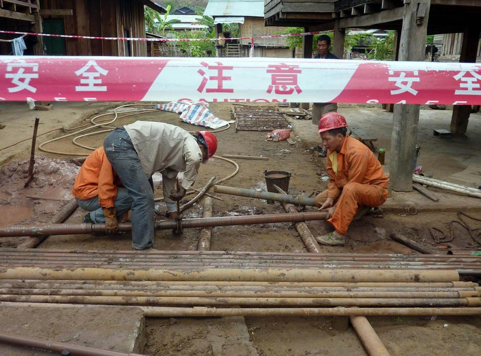Chinese workers prepare for the building of a railway linking China to Laos at Bopiat village in the Northern province of Louang Namtha