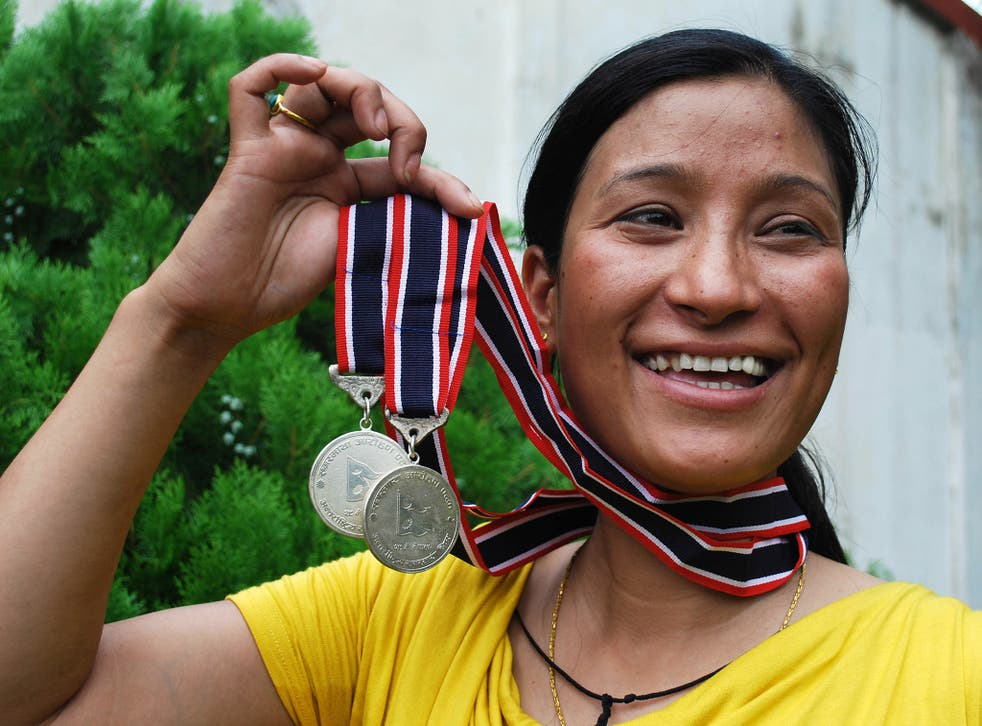 Anshu Jamsenpa holds the medals she received from the Nepalese government after climbing Mount Everest twice in 10 days in 2011.