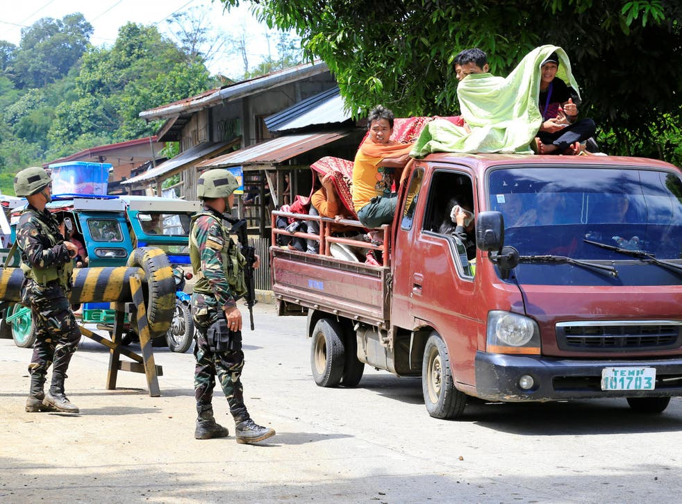 Government troops check a vehicle evacuating residents from their hometown of Marawi city in the Philippines as it drives past a military checkpoint in Pantar town, Lanao Del Norte