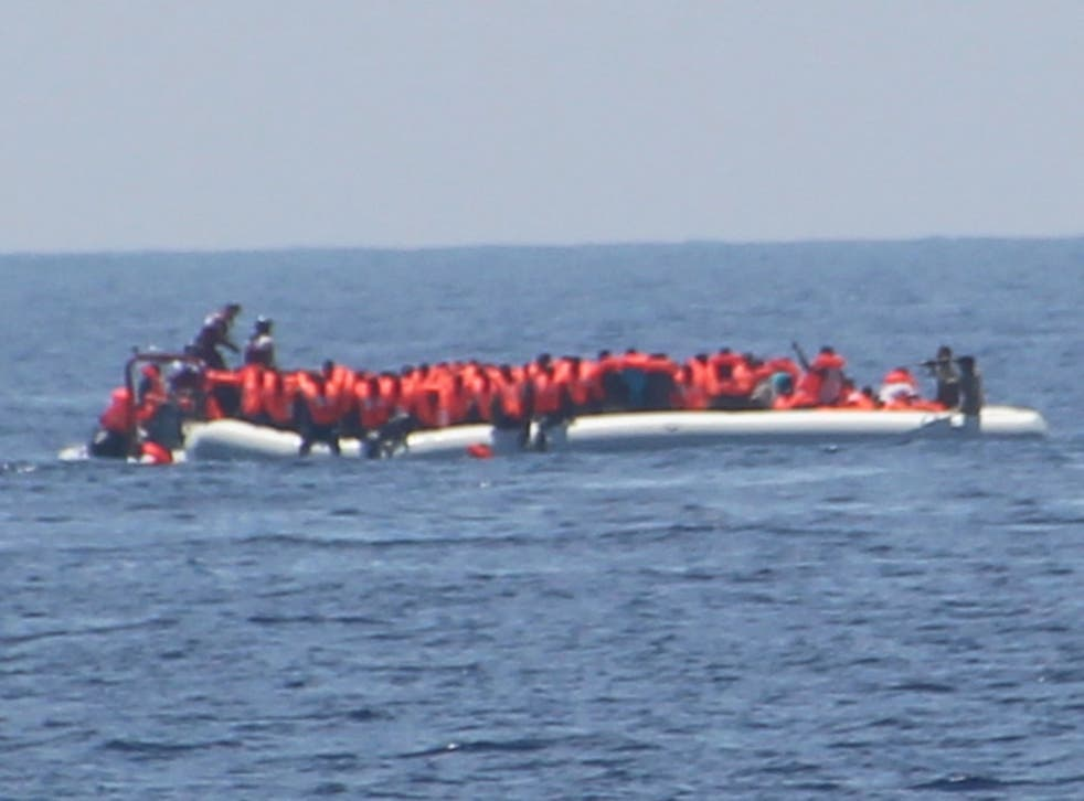 The crew of Jugend Rettet's Iuventa rescue ship photographed what appeared to be a Libyan coastguard officer pointing a weapon at refugees (far right)