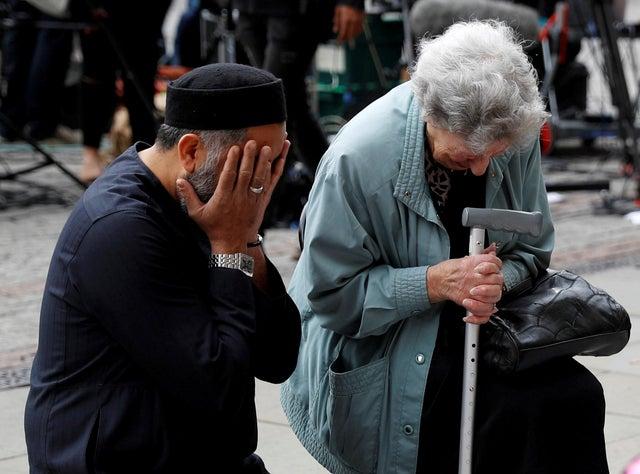 A Jewish woman named Renee Rachel Black and a Muslim man named Sadiq Patel react next to floral tributes in Albert Square
