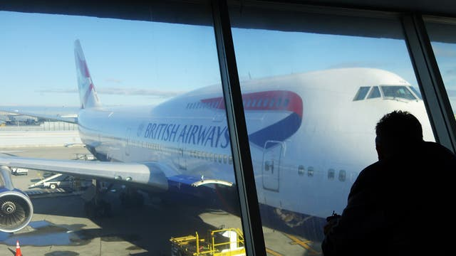 A passenger looks at a British Airway plane at John F. Kennedy (JFK) international airport in New York