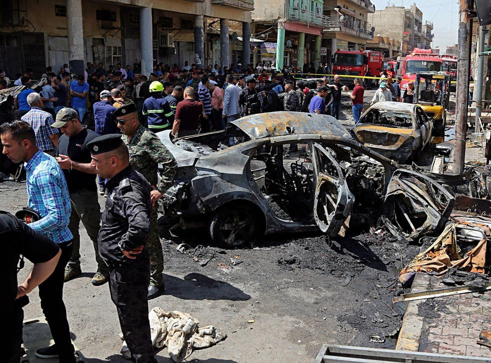 Iraqi security forces and civilians inspect the site of the second deadly bomb attack in Baghdad, Iraq