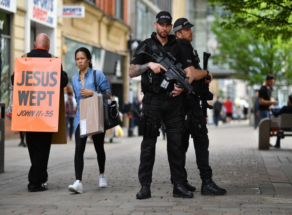 Armed police guard a street in central Manchester following the attacks
