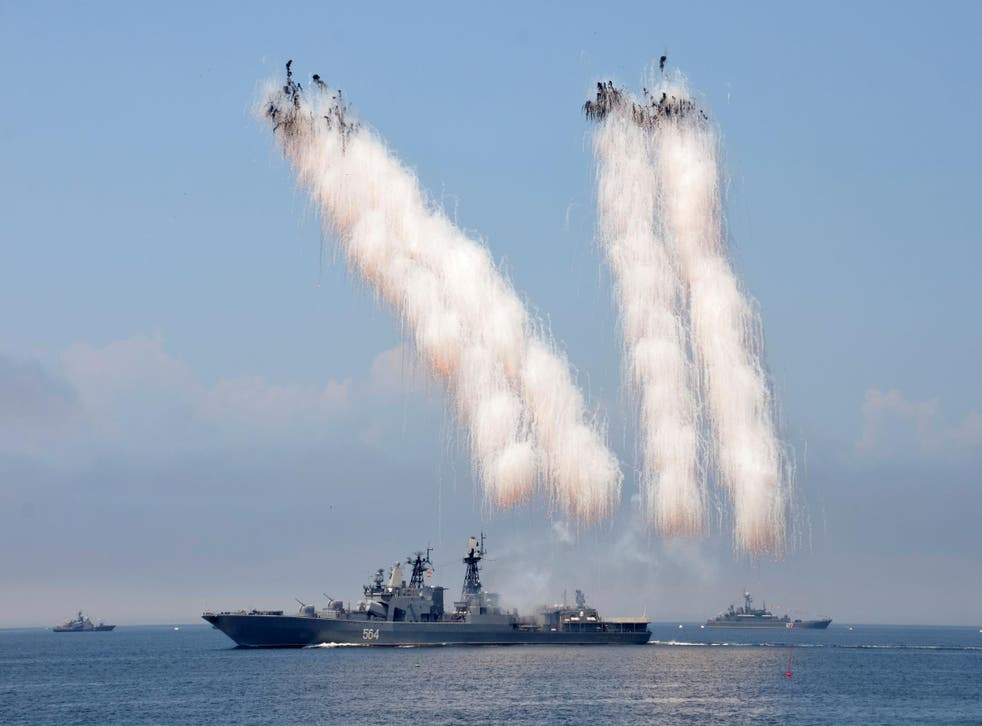 Russian warships sail past exploding anti-missile ordnance during a rehearsal for the Navy Day parade in 2016