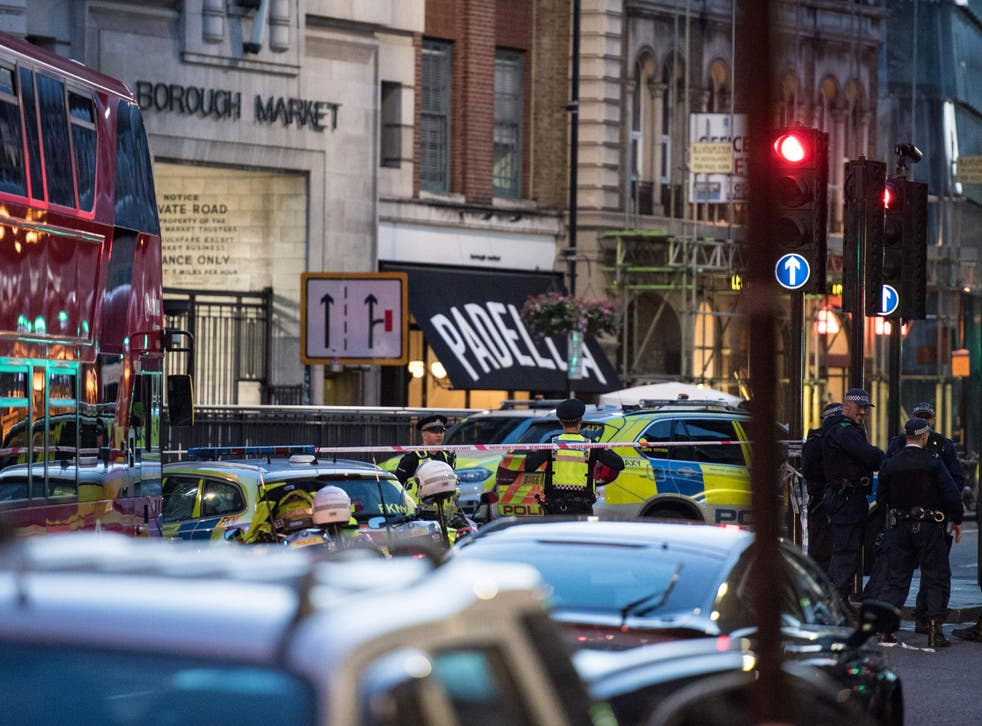 Police officers and emergency response vehicles are seen on the street outside Borough Market after terror attack