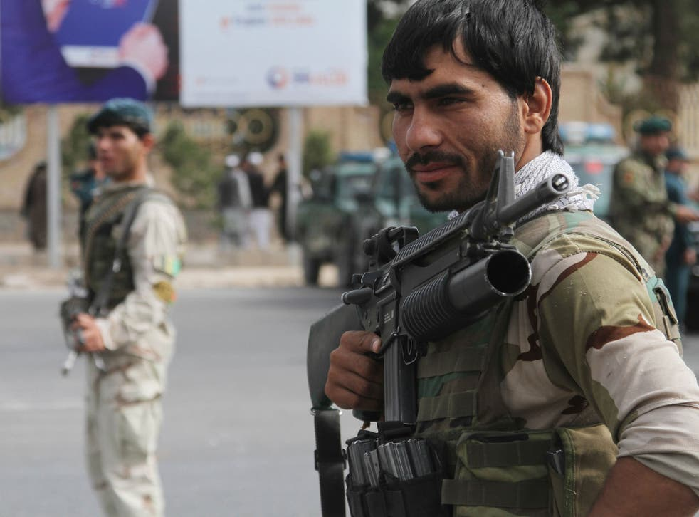 Afghan security officials stand guard at a roadside check as security has been intensified across Herat, following deadly bombings over the weekend in Kabul, in Herat, Afghanistan