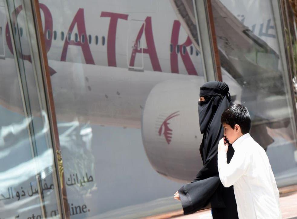 A woman and boy walk past a Qatar Airways branch in the Saudi capital of Riyadh