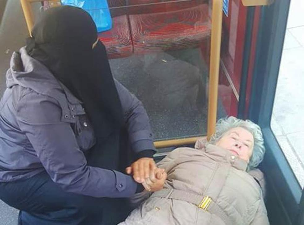 A Muslim woman (pictured left) holding hands with an elderly lady who fell over in the bus
