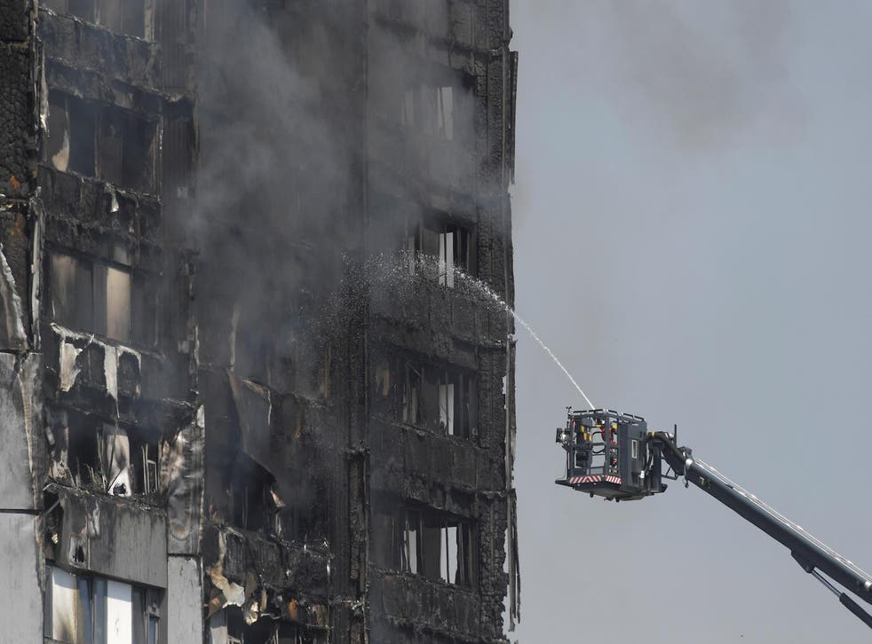 Firefighters direct jets of water onto a tower block