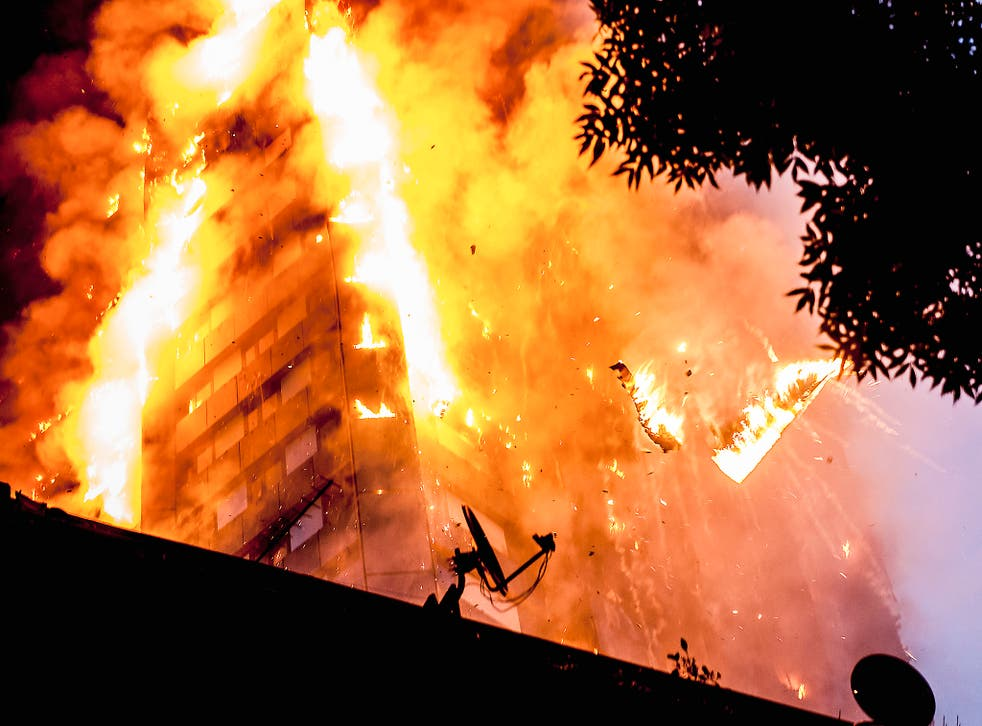 Falling burning debris at the scene of a huge fire at Grenfell tower
