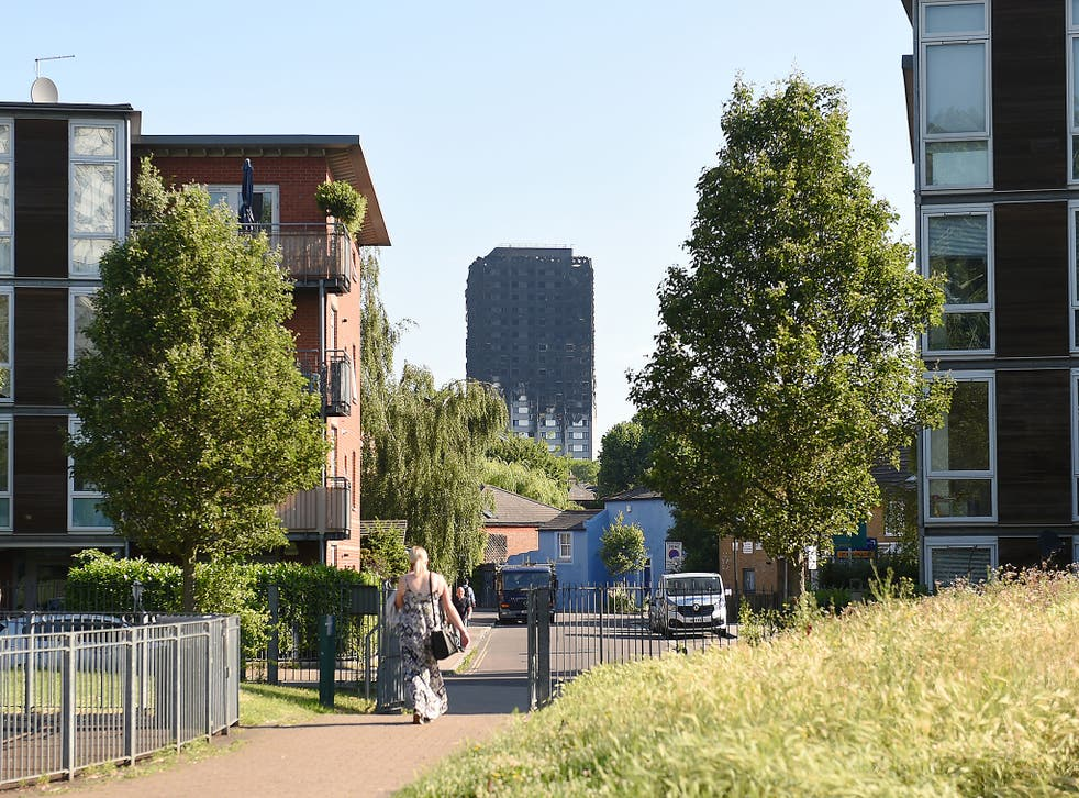 Grenfell Tower is seen in the distance, the day after the Grenfell fire