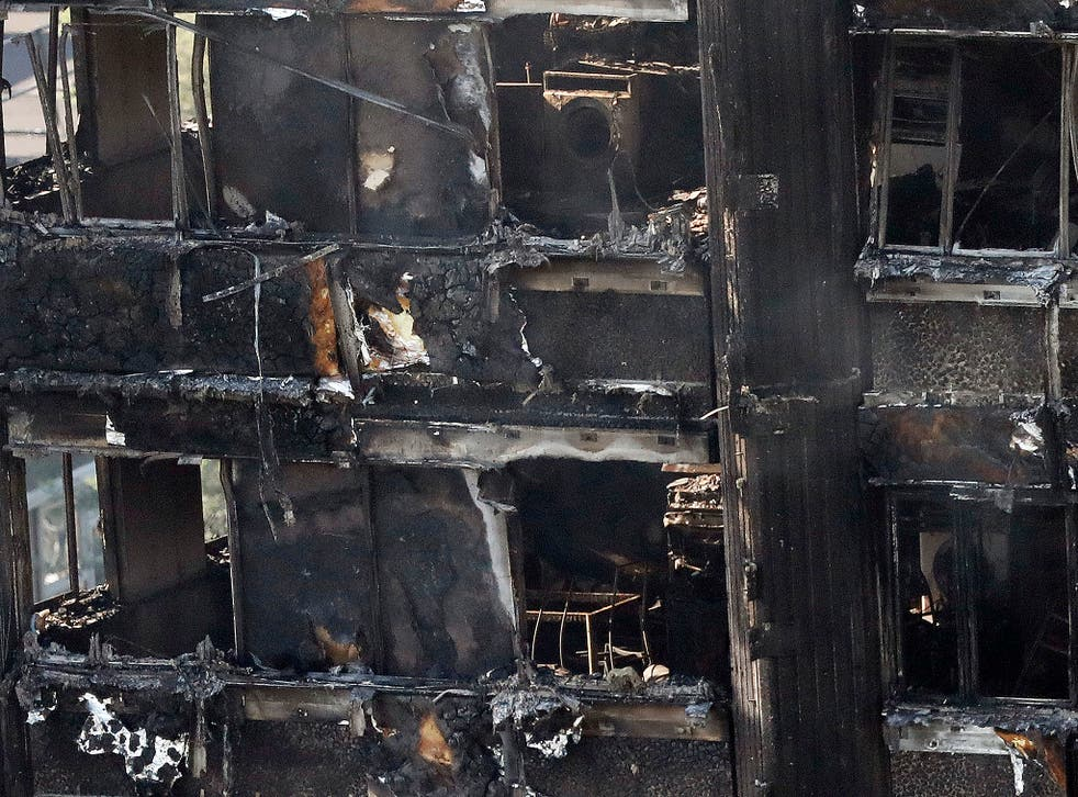 Remains of furniture are seen through the windows as smoke still emerges from the charred Grenfell Tower