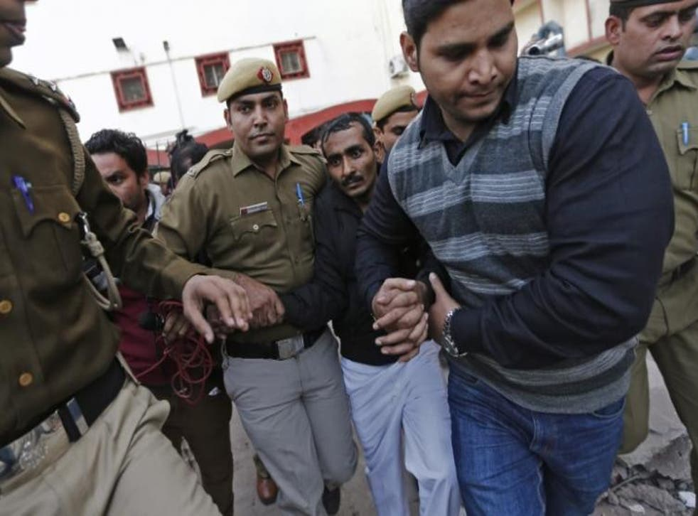Policemen escort driver Shiv Kumar Yadav (3rd right in black jacket) who is accused of a rape outside a court in New Delhi December 8, 2014