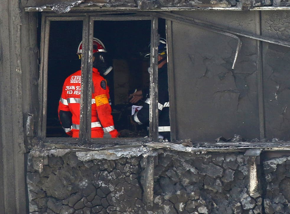 Fire service personnel survey the damage inside Grenfell Tower in west London