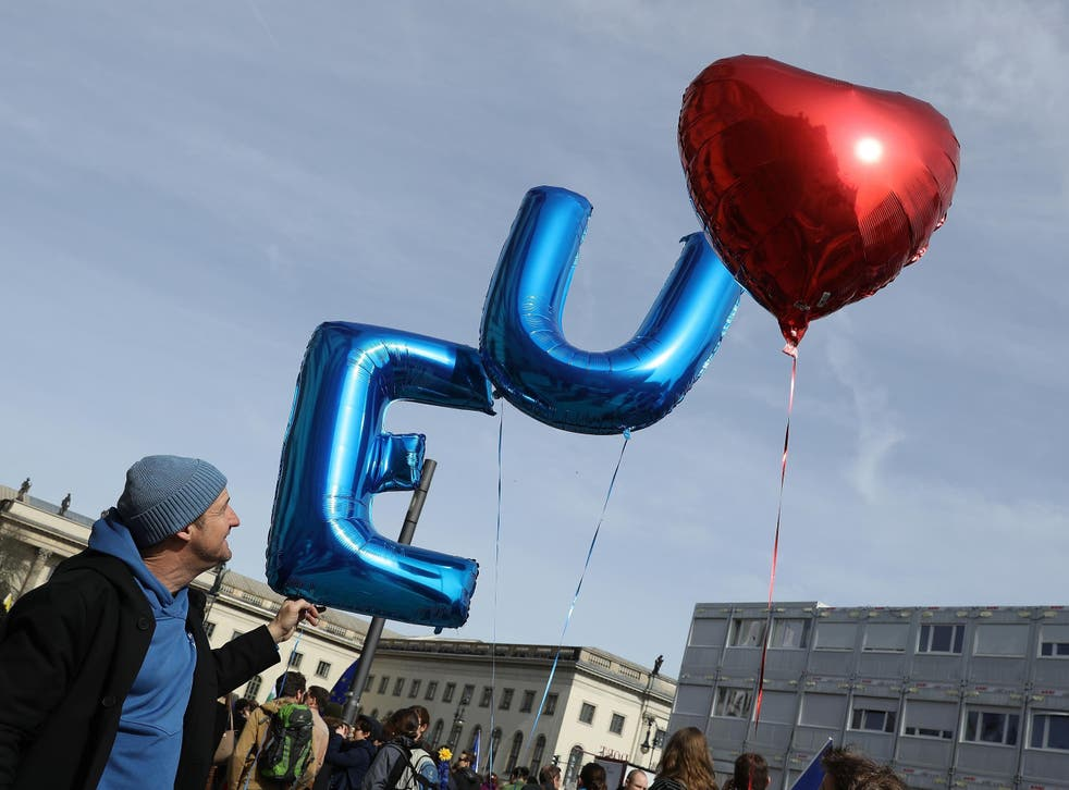 A man releases balloons at the celebration of the 60th anniversary of the Treaty of Rome