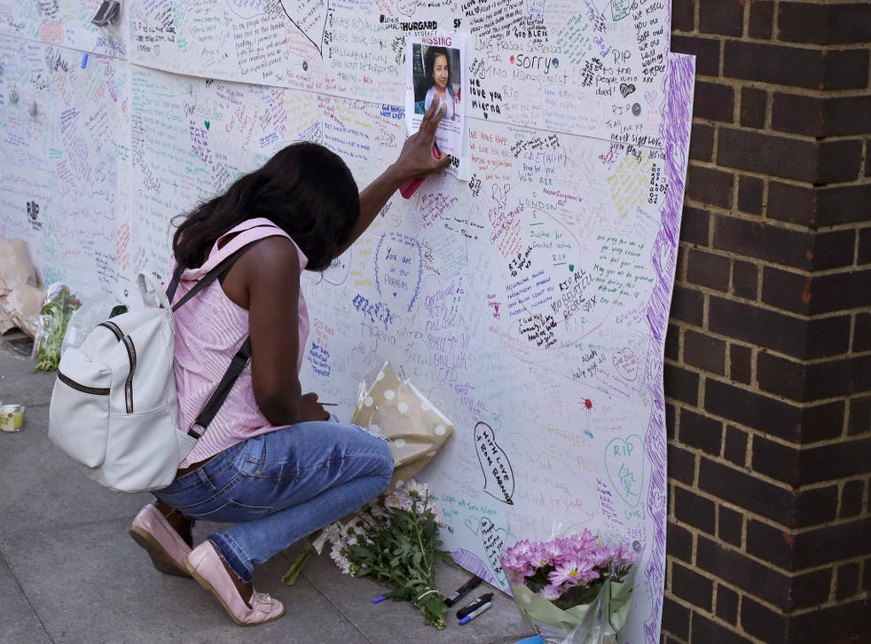 A woman touches a missing poster for 12-year-old Jessica Urbano next to the fire-gutted Grenfell Tower