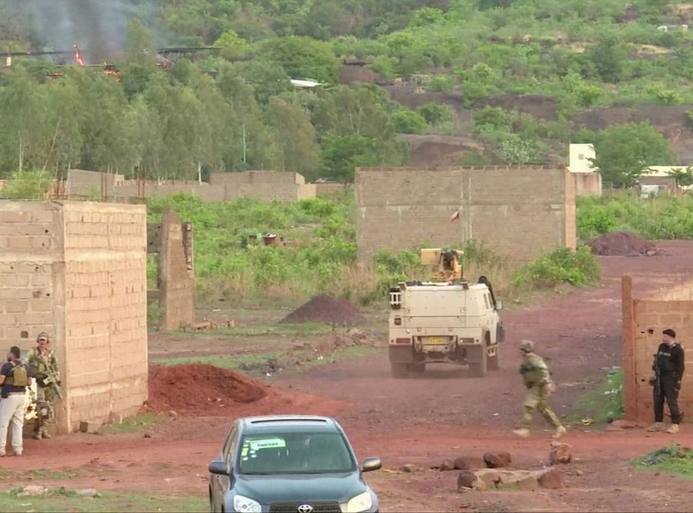 An armoured vehicle drives towards Le Campement following an attack where gunmen stormed the resort in Dougourakoro, to the east of the capital Bamako, Mali