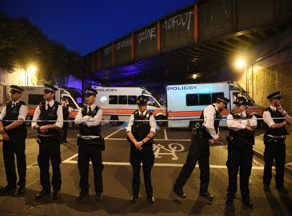 Policemen stand by a police cordon near Finsbury Park in the immediate aftermath of the attack