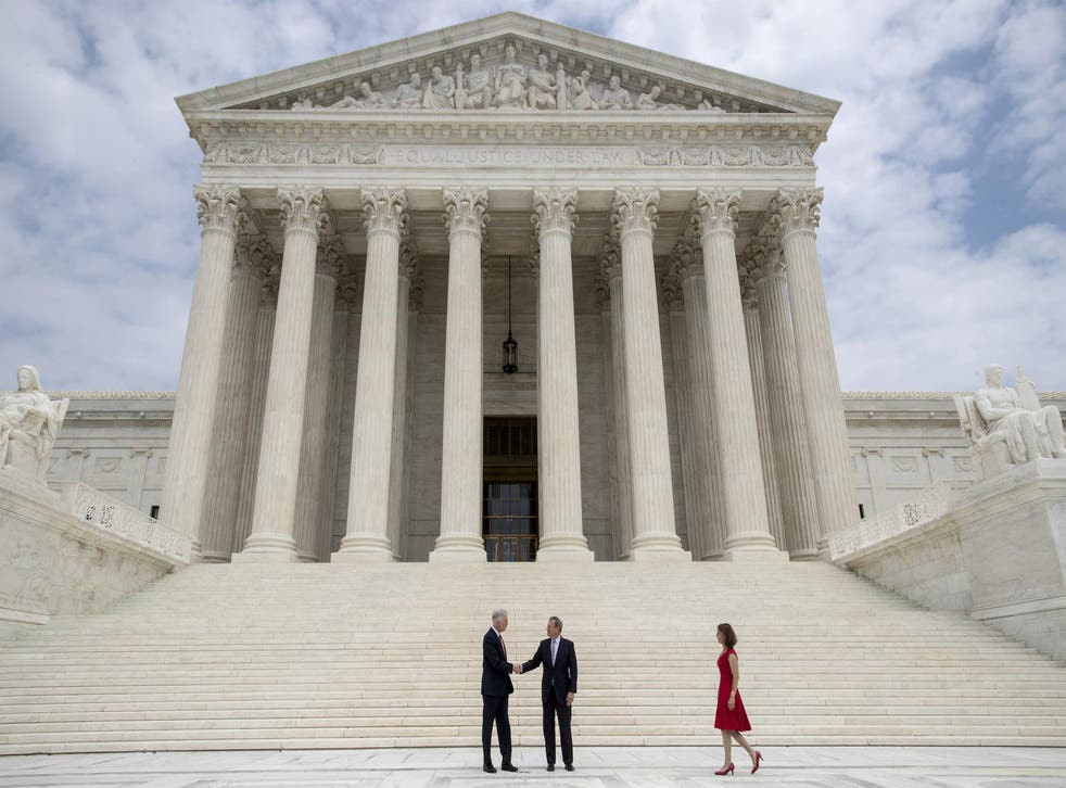 <p>Associate Supreme Court Justice Neil Gorsuch shakes hands with Chief Justice John Roberts</p>
