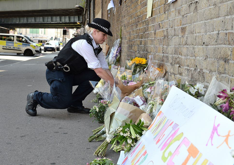 c1d29787310dc6 A police officer lays flowers passed over by a member of the public