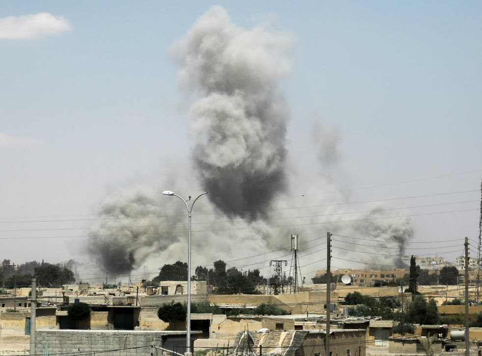 Smoke billows from buildings in the northern Syrian city of Raqqa on 18 June 2017, during an offensive by US-backed fighters to retake the Isis terror group bastion