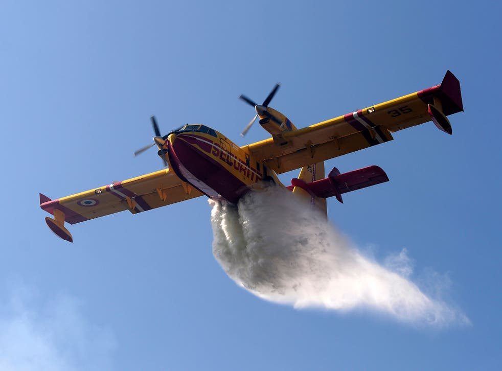 A Canadair amphibious aircraft drops its load over a wildfire in central Portugal in 2013