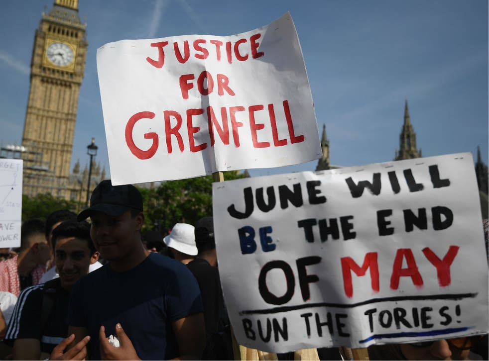 Protesters hold signs calling for a change of government and justice for the victims of the Grenfell Disaster in Parliament Square during an anti-government protest on June 21, 2017 in London, England.