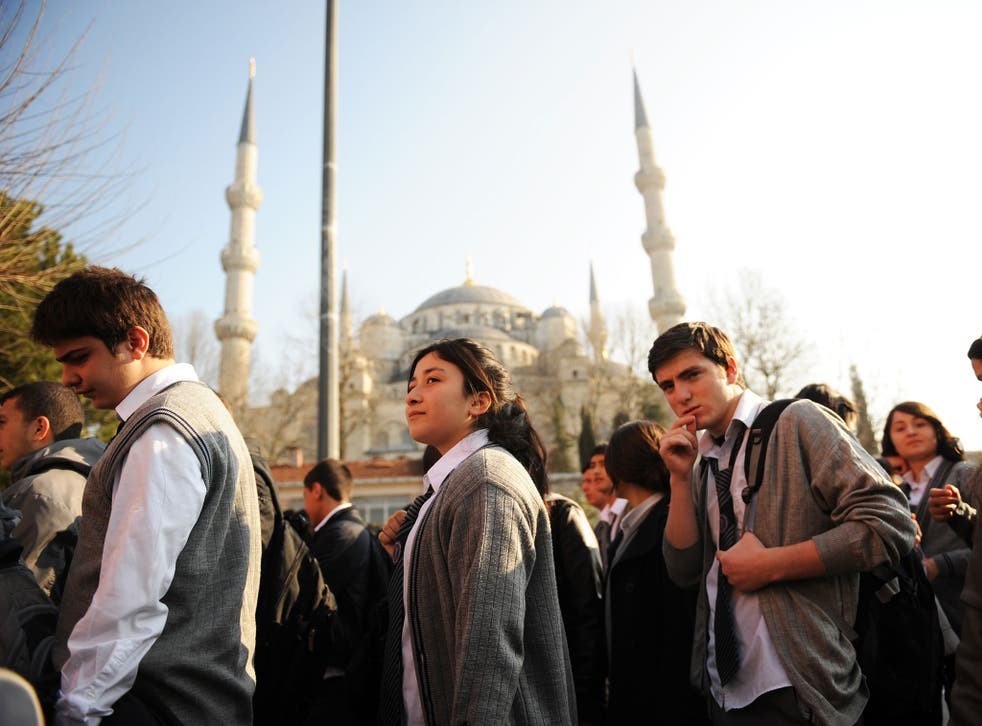 Turkish students listen to their teacher before entering their high school early in the morning in Istanbul on March 23, 2012.