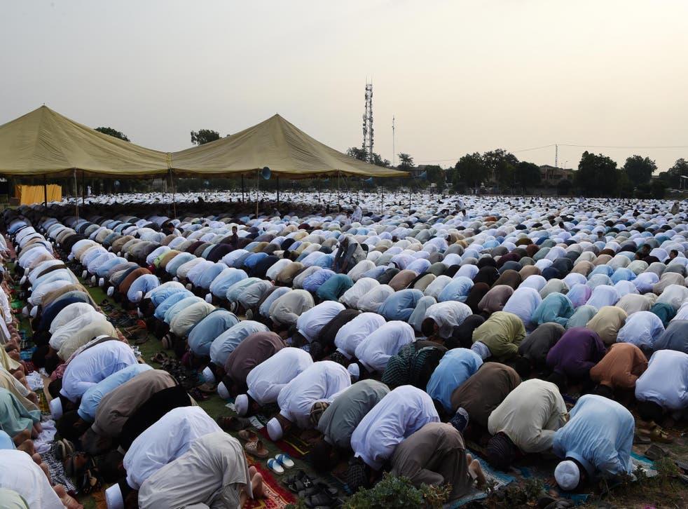 Pakistani residents offer Eid al-Fitr prayers on the outskirts of Peshawar