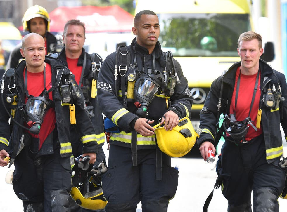 Firefighters work at the scene where a fire ripped through Grenfell Tower, on June 14, 2017