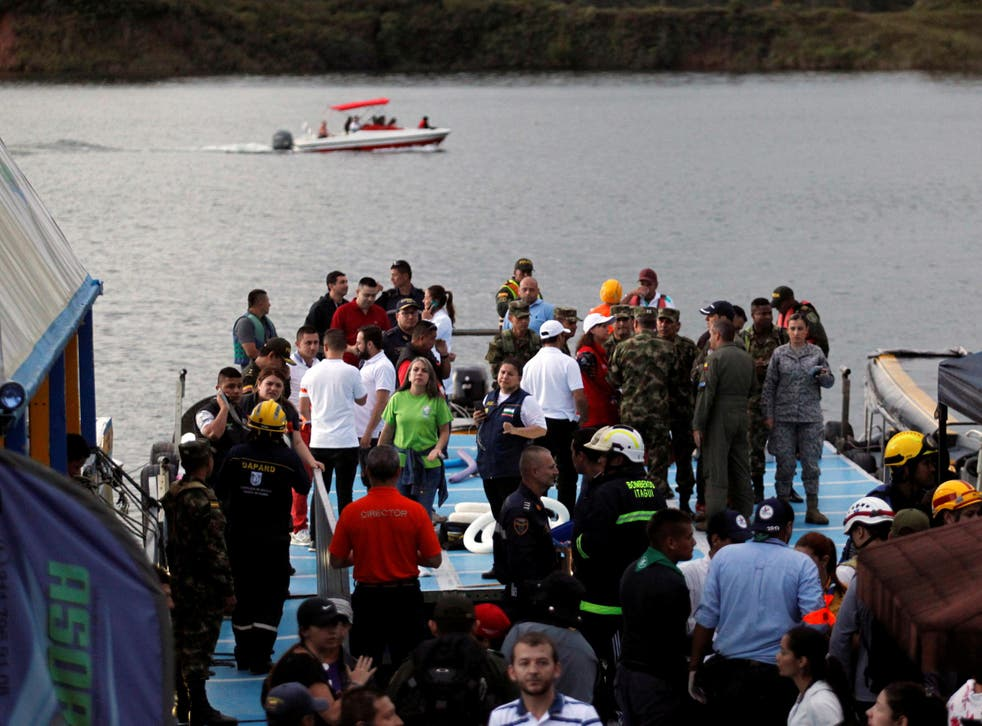 Anxious rescuer workers wait at the dock of the Guatape reservoir as a boat searches for further survivors