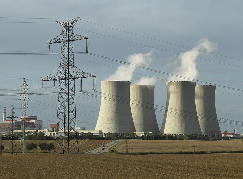 An electricity pylon stands in front of the four cooling towers and two reactor blocks of the Temelin nuclear power plant in