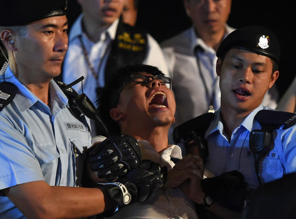 Pro-democracy campaigner Joshua Wong yells as he is taken away by police after he and other demonstrators staged a sit-in protest at the Golden Bauhinia statue, in front of the Convention and Exhibition Centre in Hong Kong