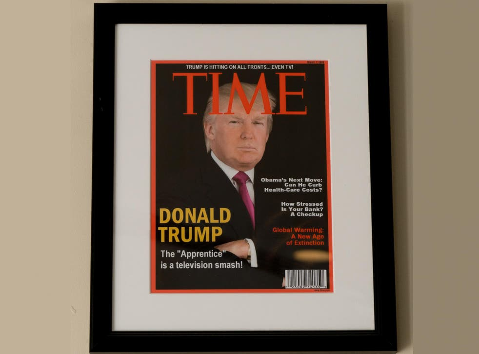 Framed portrait of President Donald Trump on the cover of a Time magazine and other magazine covers framed and hanging from a wall at the Trump National Doral Miami Golf Shop
