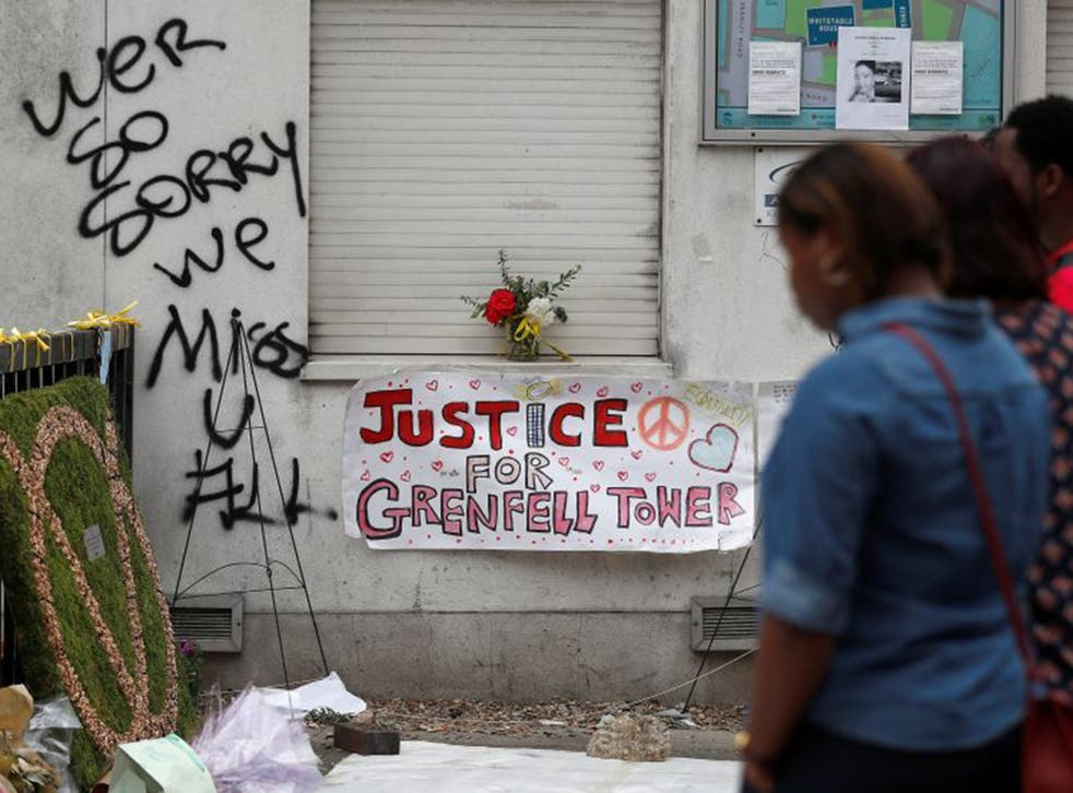 Passers-by look at posters and messages of condolence for the victims of the Grenfell Tower fire