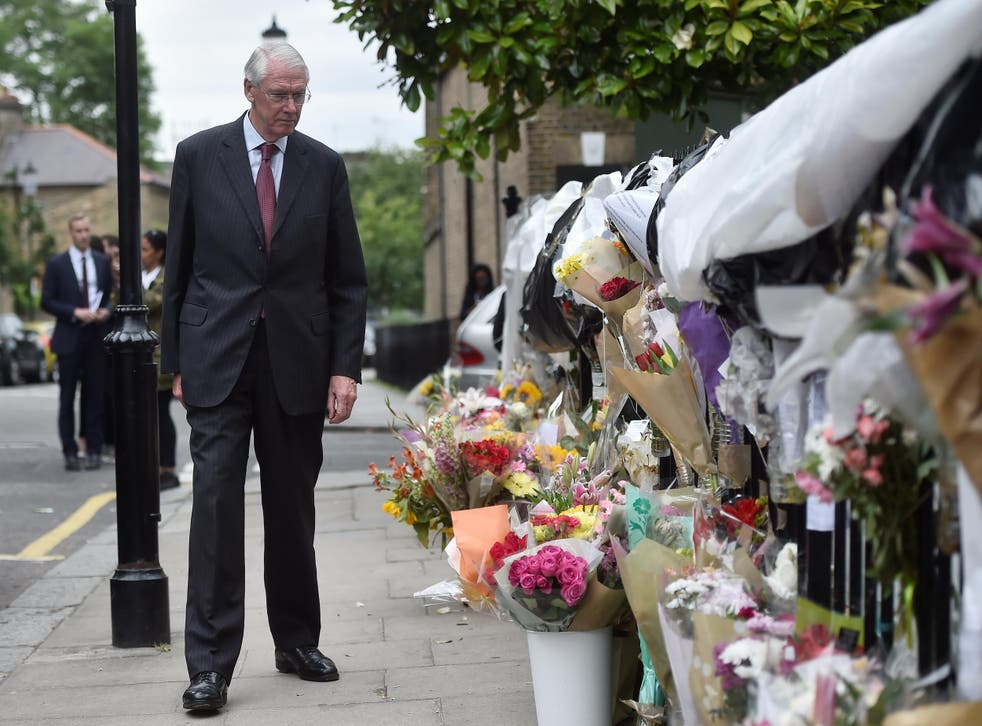 Sir Martin Moore-Bick looks at floral tributes left for the victims of the Grenfell Tower fire in North Kensington, London