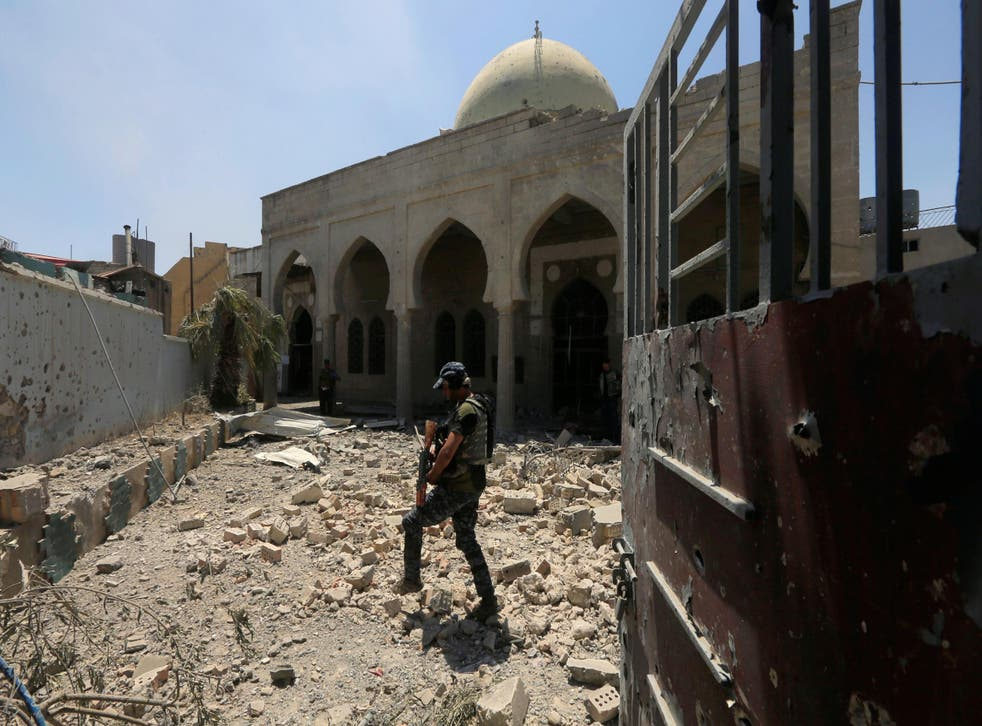 A member of Iraqi Federal Police walks through the rubble outside a mosque in Mosul's Old City