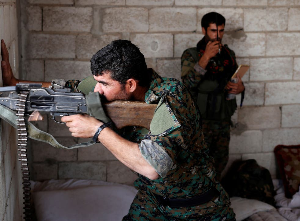 A Kurdish fighter from the People's Protection Units (YPG) fires his weapon from a house in Raqqa
