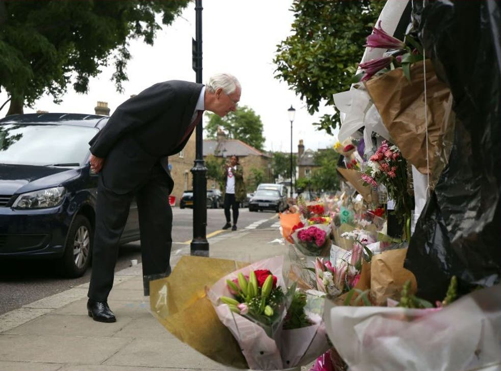 Sir Martin Moore-Bick reading floral tributes to the victims outside Grenfell Tower after meeting with residents