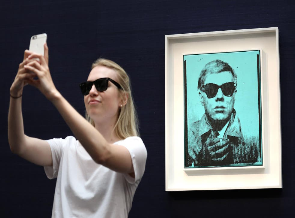 Meta: A visitor takes a selfie with one of Warhol's selfie shots
