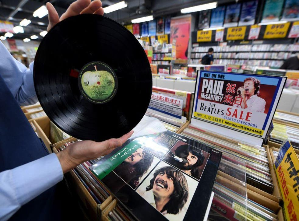 A shop manager shows off a Japanese pressing of The Beatles' final studio album Let It Be at a music shop in Tokyo's Shibuya district, Japan.