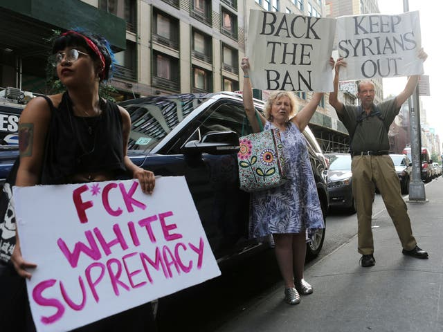 A protester against U.S. President Donald Trump's limited travel ban, approved by the U.S. Supreme Court, holds a sign next to protesters supporting the ban, in New York City, U.S., June 29, 2017